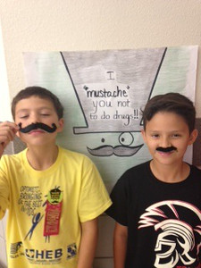 Students wearing their fake mustaches.