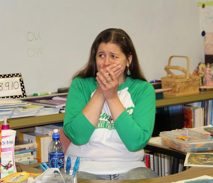 Surprised teacher holds back tears.