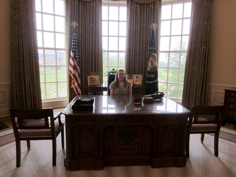 A student sitting at the presidential desk.