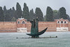 Venice; Murano Island, gulls perched on statue during squal, Cemetary Island in background