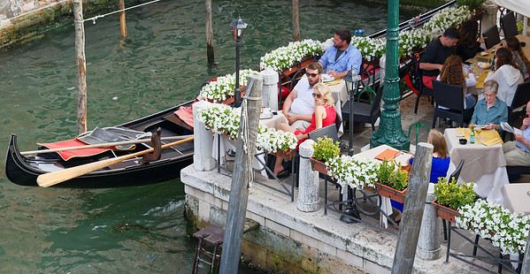 Venice; dining on the canal with a gondola moored