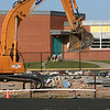 Framed by the arch of the backhoe, two Northwood students enjoy the sunshine as the old stands come down!