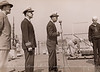 - Commission Ceremony -   Commanding Officer Lloyd Rudolph White reads his orders and assumes command of the U.S.S. LST-912 while a painter puts on the finishing touches in the background.  Commander M.C. Vangeli, U.S.N., Supervisor of Shipbuilding stands next to him.