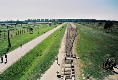 Pohled z věže na koleje vedoucí k selekci. Tady o lidech rozhodoval Josef Mengele. Vlevo, asi uprostřed je vidět barák, kde stál  a rozhodoval o tom, kdo zůstane a bude pracovat  a z koho bude za půl hodiny popel, který bude hnojit polská pole v okolí.  Krematoria jsou na konci tratě u lesa. Hořela sedm dní v týdnu, dvacet čtyři hodin denně.