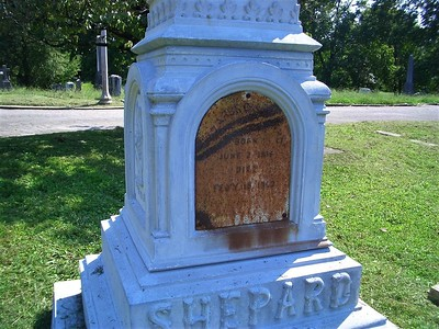 "Buried in Old Gray, Lazarus Clark (L.C.) Shepard, (1816-1902) Shepard was Knoxville's first embalmer. He made coffins and for many years was a professional undertaker. It is both ironic and perhaps fitting that a man whose name is synonymous with resurrection was in the business of interment. Shepard's tombstone is the only white bronze monument in Old Gray. Legend has it that the large hollow monument was a drop-off point for bootleg liquor during Prohibition. The rear panel shown here served as a secret compartment for alcohol and monetary exchanges, but rust over the decades has permanently sealed the metal door. Shepard was born in Newtown, CT, and attended common schools there until age 15 when he apprenticed at his father's wood-working establishment. After learning the trade of a wood turner, he was made a partner in the business which soon added a rail car foundry. At 21, he married Emily Strong of Bridgeport, CT. They lived in Bridgeport for 17 years, had five children there, and, in 1854, moved to Knoxville where Shepard started a wood-working business on South Gay Street. The shop burned four years later, and he then became foreman of the rail car building department for the E.T.V.&G railway which had just extended its lines to Knoxville. After nine years with the railroad, Shepard spent some time connected with the Knoxville rolling mill and in 1867 then embarked in the furniture business, adding to this a plant for the manufacture of coffins. He became Knoxville's first resident undertaker and was noted with conducting the funeral of President Andrew Johnson in Greeneville, TN, in 1875. In 1884 he joined Edward Mann and Thomas Johnson to form Knoxville's first formal undertaking establishment, Mann & Johnson. In 1892, Shepard and Johnson retired. Shepard was one of the organizers and charter members of the first I.O.O.F. (Independent Order of Odd Fellows) lodge instituted in Knoxville, was three times an alderman of the seventh ward and was a trustee of the Tennessee School for the Deaf and Dumb. He was a member of Broad Street M.E. church and for many years was a warden. Shepard's obituary in the The Journal and Tribune (2/16/02) said that in late life he made a bad business investment and was never employed after that. Notice of his death in The Tennessean said that he died a pauper. We don't know what the bad business investment was; his ads for undertaking services were still appearing in TN newspapers as late as 1883. Shepard's wife Emily was also known for her civic contributions. She ""aided"" (how unclear) the establishment of the Industrial Home for Youths which 3 yrs after her death became (with funding by Charles McClung) St. John's Orphanage. As a member of the Ladies Memorial Association, she was instrumental in getting the Confederate memorial in Bethel Cemetery. She also tried to establish a home for ""unfortunate women"" but failed to get funding. She died in 1882 and is buried in Old Gray with her husband. Her obituary noted a ""lengthy funeral cortege"" followed her hearse to Old Gray, her pallbearers were several of Knoxville's most prominent citizens, and Dr. Thomas W. Humes, President of the University of TN, officiated at her funeral."