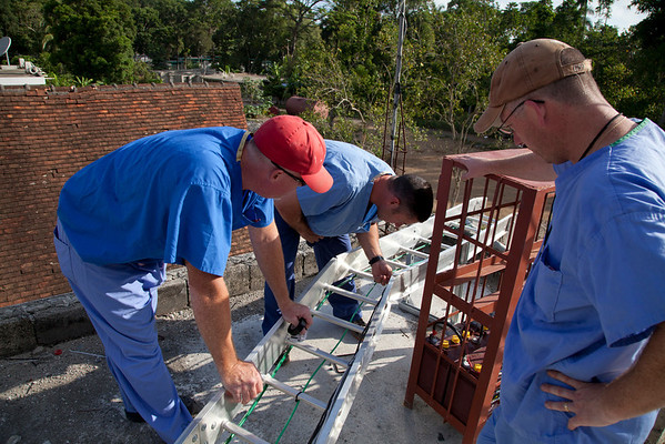 Jimmy Candella (center) and Cyril Coffey (right) work on communication lines at Hopital Sacre Coerur in Milot, Haiti. A team of Holy Name Medical Center employees traveled to  Milot, Haiti to run new electric and communications cable, and get a pair of generators installed and operational. The team employed and taught a crew of local Haitian workers on the projects.<br /> Photos from Hopital Sacré Coeur, the CRUDEM foundation, and Holy Name Medical Center's involvement in Milot, Haiti.  Photo by Jeff Rhode / Holy Name Medical Center 9/6/12