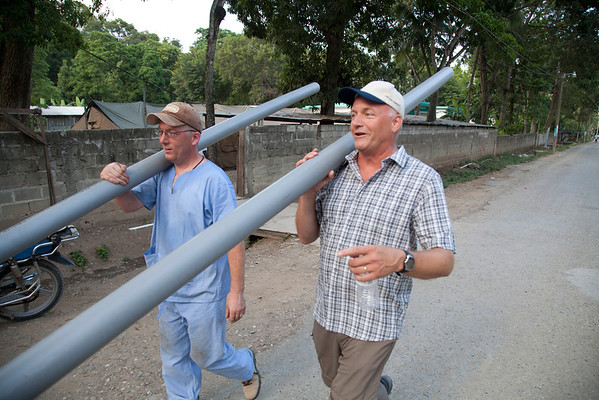 (LtoR) Cyril Coffey and Mike Maron carry PVC conduit to a construction site in Milot, Haiti. A team of Holy Name Medical Center employees traveled to  Milot, Haiti to run new electric and communications cable, and get a pair of generators installed and operational. The team employed and taught a crew of local Haitian workers on the projects.<br /> Photos from Hopital Sacré Coeur, the CRUDEM foundation, and Holy Name Medical Center's involvement in Milot, Haiti.  Photo by Jeff Rhode / Holy Name Medical Center 9/4/12