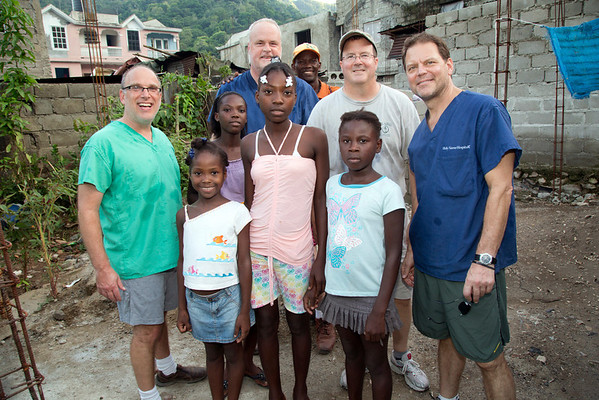 Dr. Adam Jarrett, Tom Wall, Dr. Steve Wells, and Dr Chris Englert at the home with the family of a friend in Haiti. Photos from Hopital Sacré Coeur, the CRUDEM foundation, and Holy Name Medical Center's involvement in Milot, Haiti.  Photo by Jeff Rhode / Holy Name Medical Center 10/25/13