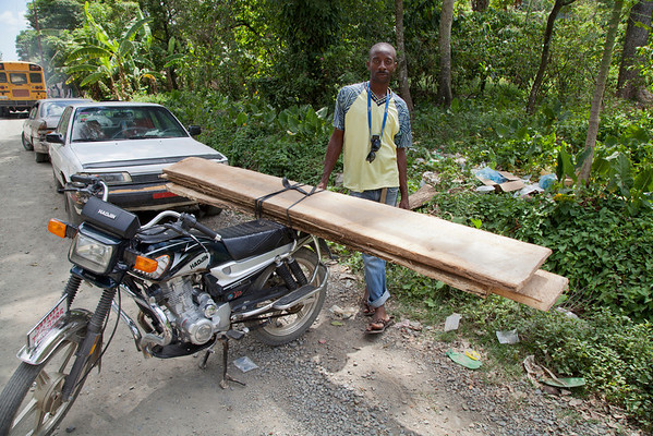 A man straps 8 foot long boards to his motorcycle to move them. It s not uncommon to see several people and cargo on a small motorcycle.<br /> Photos from Hopital Sacré Coeur, the CRUDEM foundation, and Holy Name Medical Center's involvement in Milot, Haiti.  Photo by Jeff Rhode / Holy Name Medical Center 9/6/12