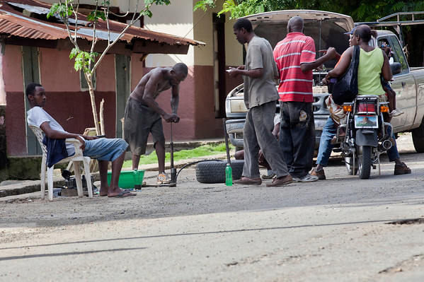 Men on the street fixing a flat tire in Milot, Haiti. Photos from Hopital Sacré Coeur, the CRUDEM foundation, and Holy Name Medical Center's involvement in Milot, Haiti.  Photo by Jeff Rhode / Holy Name Medical Center 10/24/13
