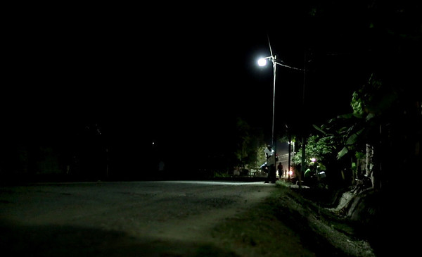 Children do homework under a streetlight in Milot, Haiti. Most people do not have electricity, and once the sun goes down the only light is one of the dozen lights on the street powered by the Hopital Sacré Coeur generators. <br /> Photos from Hopital Sacré Coeur, the CRUDEM foundation, and Holy Name Medical Center's involvement in Milot, Haiti.  Photo by Jeff Rhode / Holy Name Medical Center