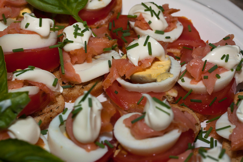 Ducktrap smoked salmon canapes with creme frech, chopped chives, hard boiled egg, heirloom, sliced tomato,  and basil atop custinis, a traditional, celebratory food for Christmas and other holidays. These aren't difficult to assemble and make a showy cocktail party food.