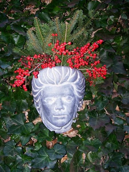 stone wall sconce filled with winter berries on ivy wall