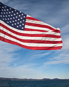 American flag, Old Glory, waving from ferry to Vinalhaven, Maine with Camden Hills in the background, Penobscot Bay