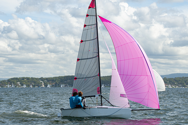 Two school kids sailing small sailboat with a fully deployed vib