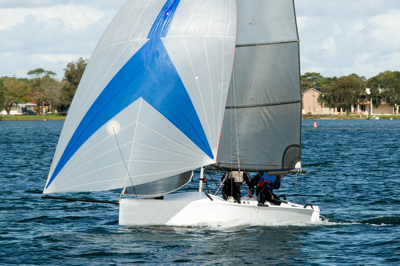 Colourful sailing dingy with blue and white spinnaker being navigated by junior sailors