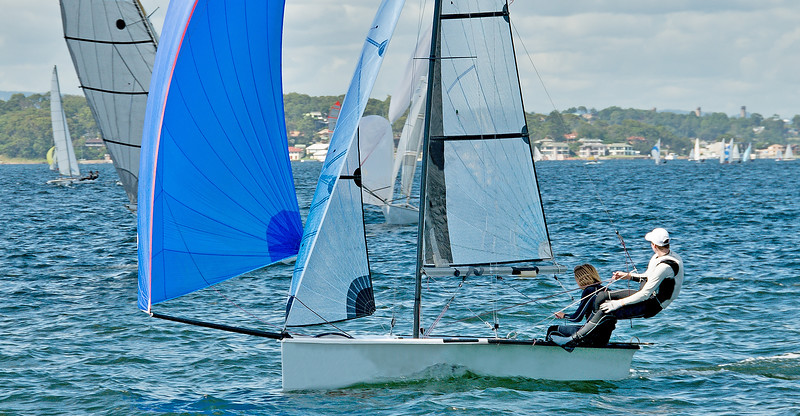 Children sailing / racing small sailboat with a blue spinaker on a coastal lake. Commercial use photo.