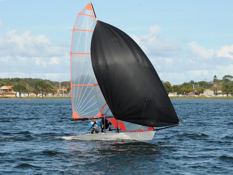 Kids racing a small sailboat with a Black spinnaker at a Junior yachting regatta on a coastal lake.