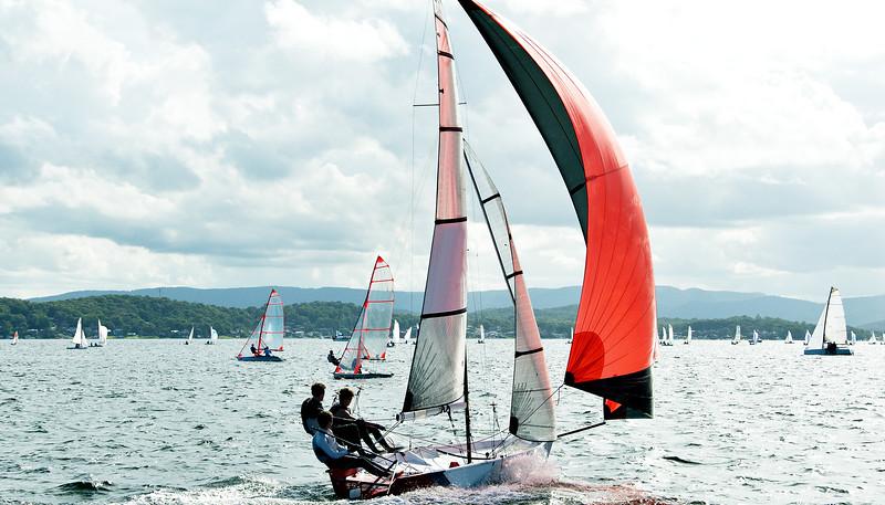 Three high school boys competing in a sailing regatta closeup at speed. Australia.