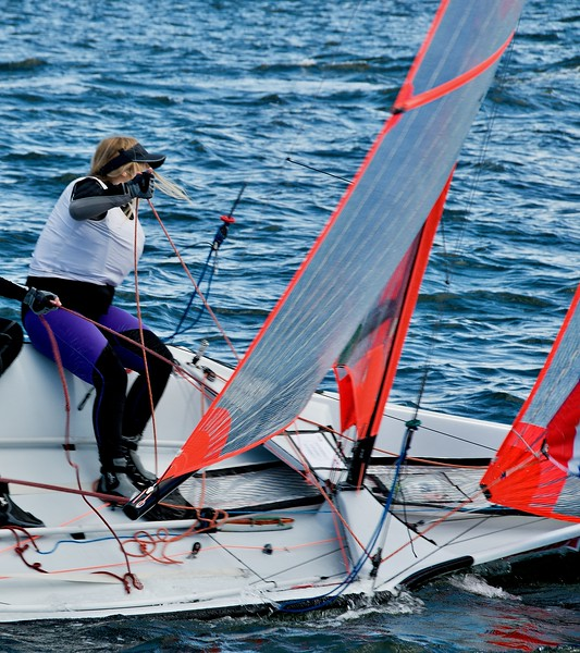 Female sailing a racing dinghy with a milar sail on an inland waterway.