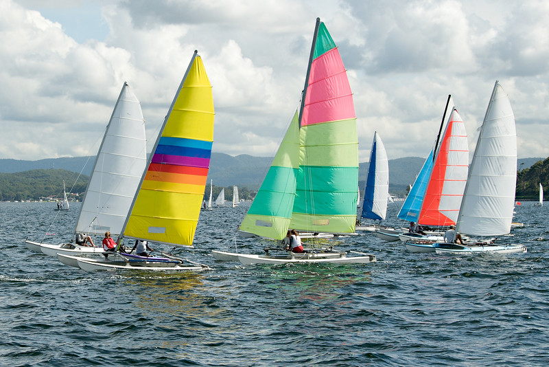Children Sailing small sailboats with colourful sails on an inland waterway.