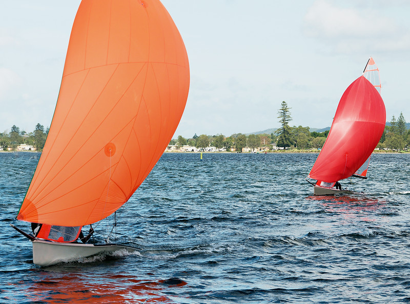 Children Sailing small sailboat with colourful orange and red sails on an inland lake.