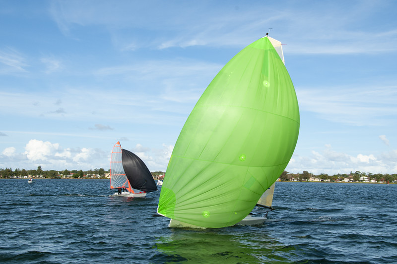 Kids sailing small sailboat head-on closeup with a fully deployed lime green spinnaker.