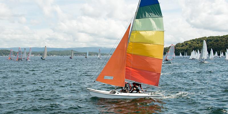 Childern racing sailing a small catamaran sailboat with colourfu