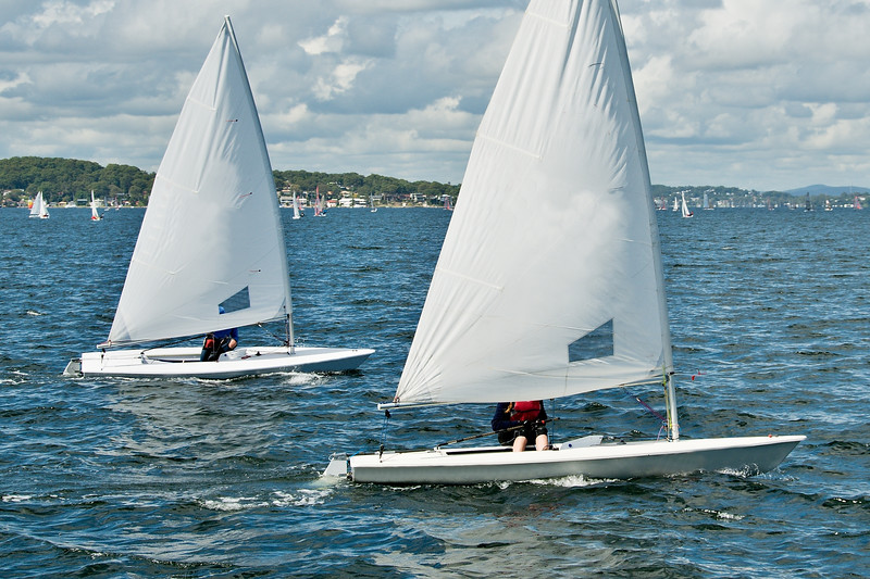 Teens racing in small sailboat with white sails on an inland waterway. Commercial image.