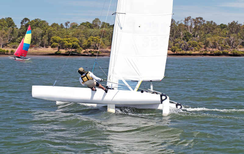 Youth Sailing small catamaran boat with a white sail on an inland waterway.