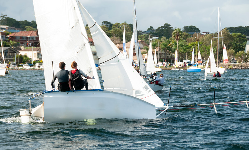 Children about to capsize a small racing sailboat. Commercial use image.