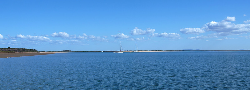 Blue sky nautical tropical island waterscape.