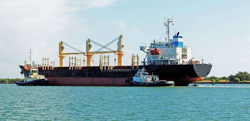 A 140 meter Bulk Carrier Ship being managed by tugboads in the Burnett River. Bundaberg, Australia.