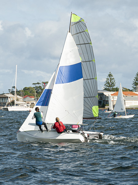 Children racing two sailboats close, side by side almost touchin