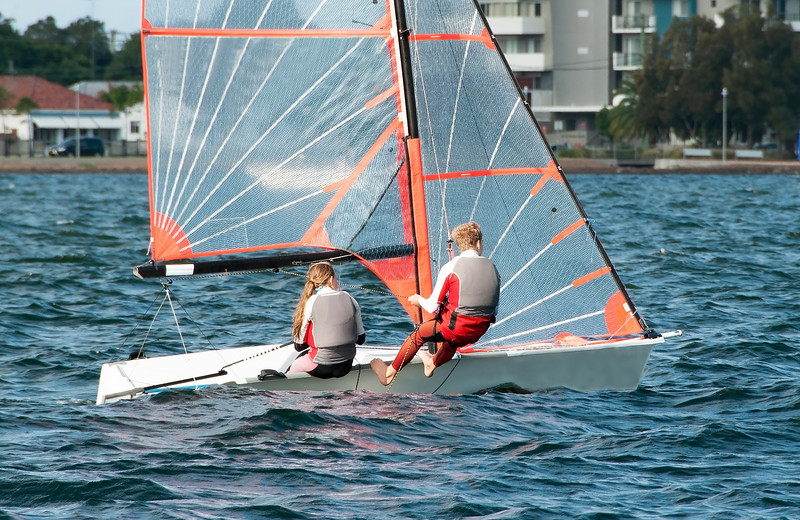 High school students Sailing small sailboat in competition on a saltwater lake.