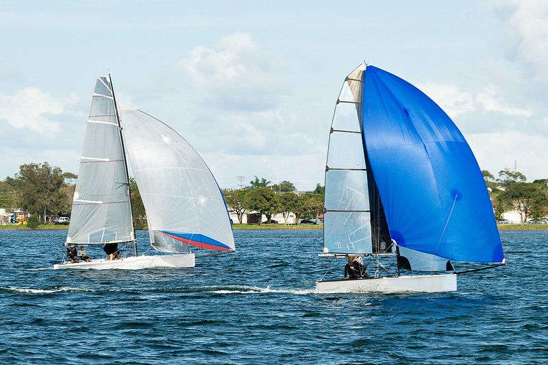 Two sailing dinghies racing at a childrens yachting regatta. Commercial use photo.
