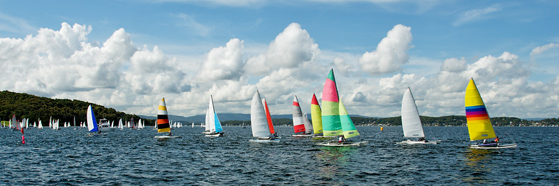Regatta Panorama. Children Sailing small sailboats (Catamarans) with colourful sails. Australia. Commercial use image.