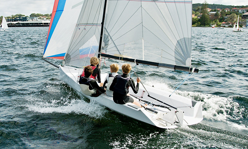 Boys flat chat sailing / racing a small sailboat in a coastal lake. Commercial image.