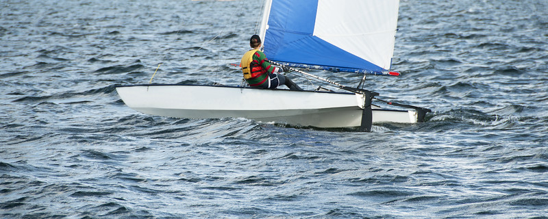Child Sailing small catamaran sailboat with a blue and white sail on an inland waterway.