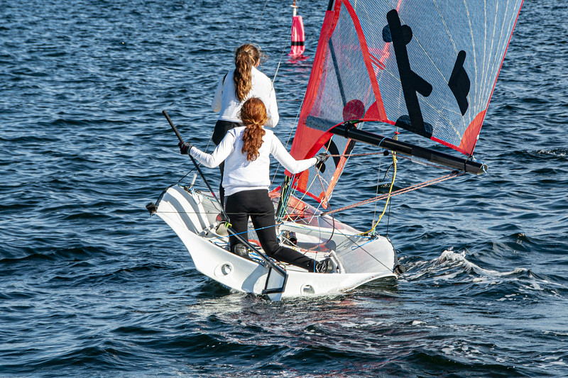 Two Girls Sailing small sailboat with long red hair viewed closeup from behind.