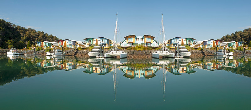 Waterfront maritime resort marina/dock with boats clear water reflections. Commercial image.