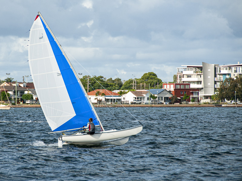 Boy sailing small catamaran at speed with vivid blue and white s
