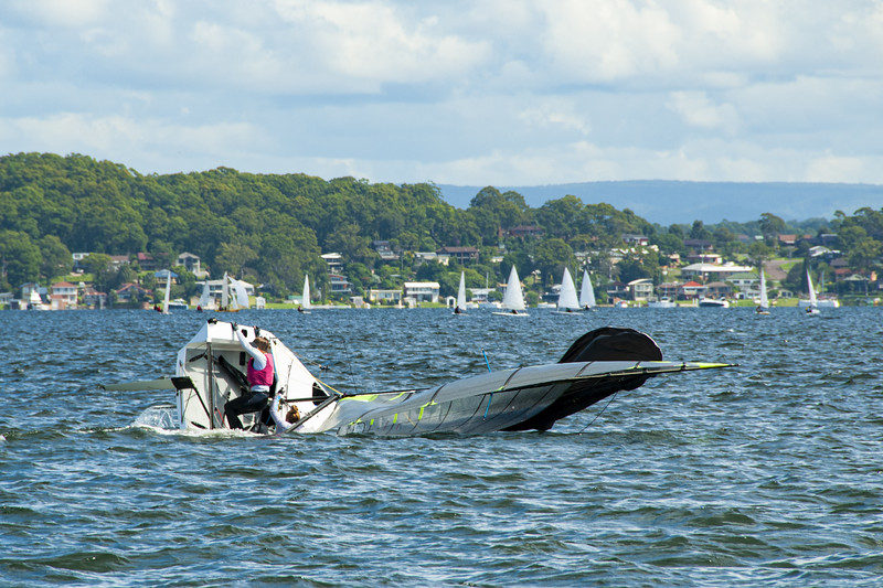 A junior sailor climbing back onboard a capsized sailing skiff.