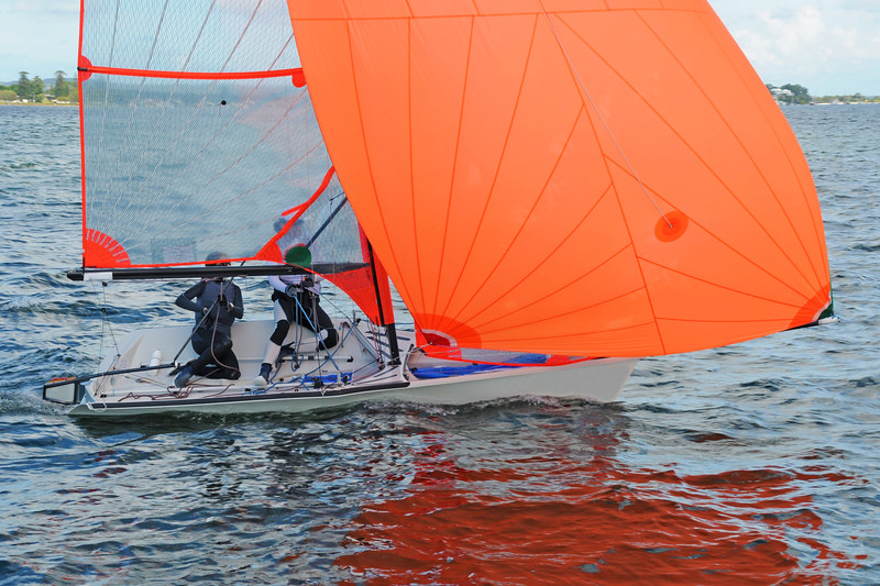 Two children sailing a racing dinghy with a large fully deployed orange coloured spinnaker.