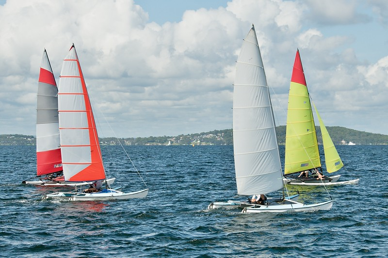 Children Sailing small catamiran sailboats with colourul sails.