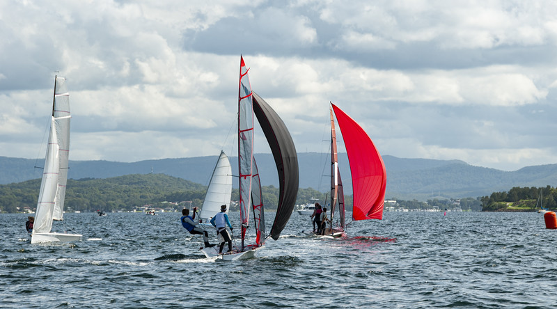 Children sailing racings sailboats with colourful sails on an in