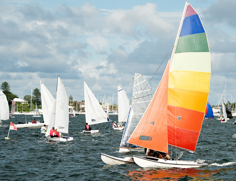 Racing Cat sailboat closeup with a bright multicoloured sail competing in a junior sailing regatta. Australia. Commercial use photo.