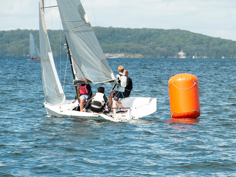 Young boys Sailing / Racing small sailboat, rounding an orange marker. Commercial image.