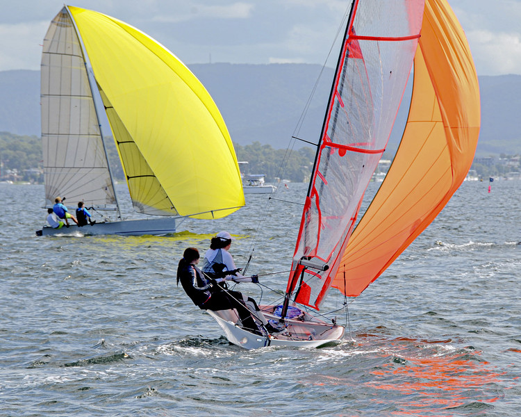 Children Sailing small sailboats with yellow and orange sails on an inland waterway.