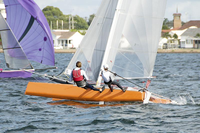 Children Sailing a catamaran sailboat at speed with one hull air